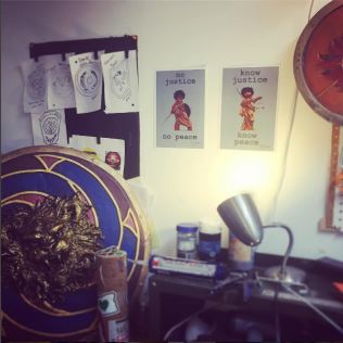 My new space with orders on the wall, a shield ready to ship, and some wal-art for fighter inspiration from IRL SJwarriors.